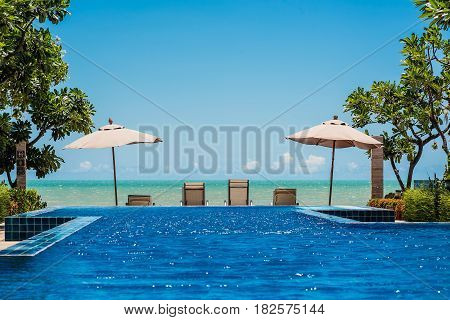 Tropical beach resort with lounge chairs and umbrella with the sea and blue sky background Cha-am - Hua Hin Thailand