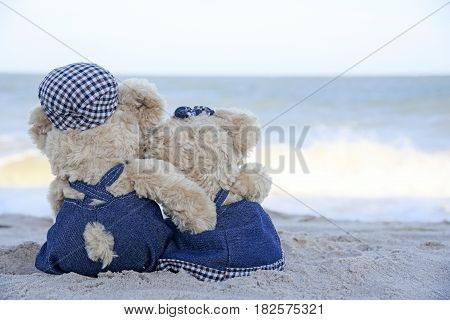 Two teddy bears sitting on the beach and see blue sky and sea Love Concept