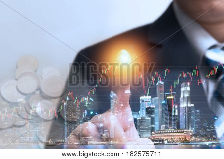 Financial trading stock concept with businessman touching hologram screen with orange light in finger to check worldwide currency market stock data over cityscape night view