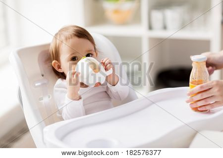 childhood and people concept - little baby drinking from spout cup sitting in highchair at home