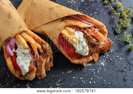 Greek Gyros Wrapped In Pita Breads On A Black Dish