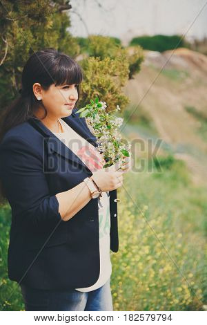 Happy Smiling Beautiful Overweight Young Woman In Dark Blue Jacket Outdoors With Flowers. Confident