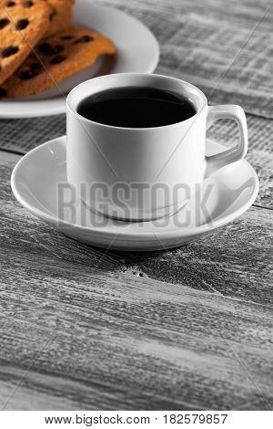 cup of coffee with a brown cookie on a wooden table