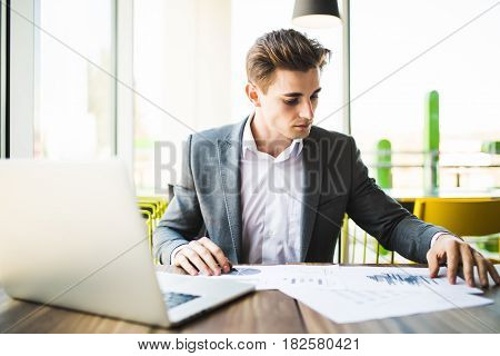 Businessman With Laptop Computer And Papers Working In Office
