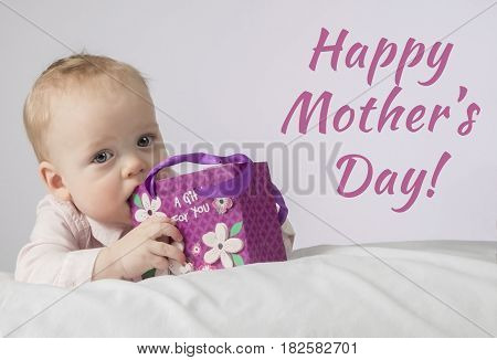 Happy Mothers Day. Cute 8 Month Boy With A Gift In A Pocket Lying On The White Blanket And Looking A