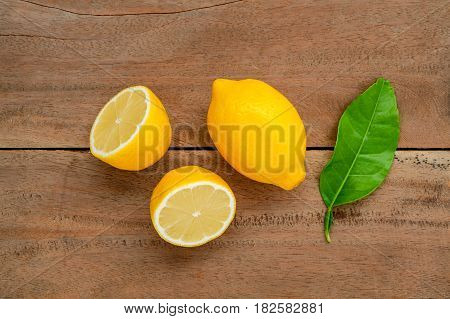 Fresh Lemons And Lemons Leaves On Rustic Wooden Background. Fresh Lemons And Lemon Slice On Wooden T