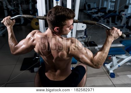 Fitness man with a naked torso trains on cable machine in the gym close-up