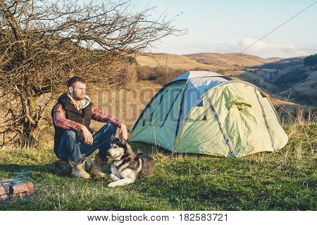 Guy bearded in jeans checkered shirt and a sleeveless jacket with a dog husky on vacation sitting on nature next to the tent in the evening at sunset.