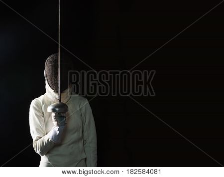The portrait of woman wearing white fencing costume and black fencing mask with the rapier on black background