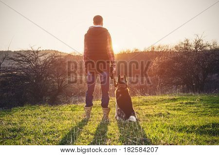 A man with a beard walking his dog in the nature, standing with a backlight at the rising sun, casting a warm glow and long shadows against the background of the gorge and trees on caucazus