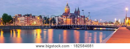 Night panoramic city view of Amsterdam canal, bridge and Basilica of Saint Nicholas, Holland, Netherlands. Long exposure. Used toning