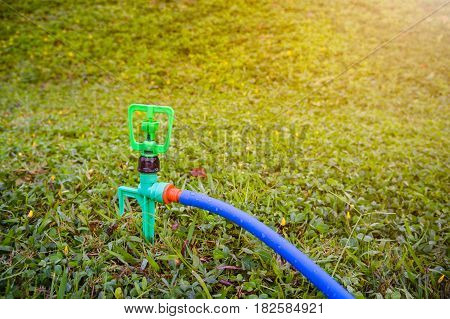 Gardening. Lawn automatic sprinkler on green grass with bright sunlight. Irrigation system - technique of watering in the garden. Outdoor at the daytime on summer day.