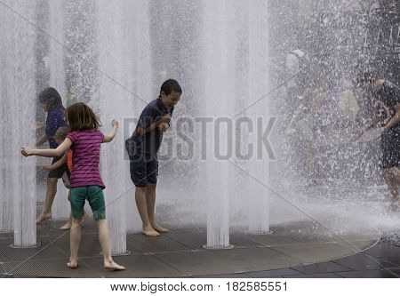 Montreal, Quebec - June 27, 2015 - Wide view of children playing in the automated water fountains at the International Jazz Festival in downtown Montreal, Quebec on a bright day at the end of June.