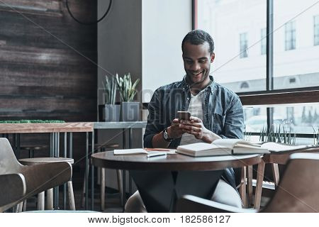 Always in touch with friends. Good looking young African man using his smart phone while sitting at his working place in the cafeteria