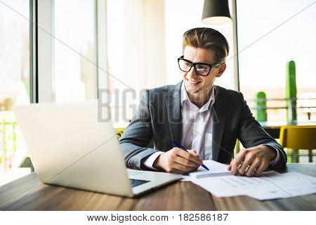 Business Man Working At Office With Laptop And Documents On His Desk.