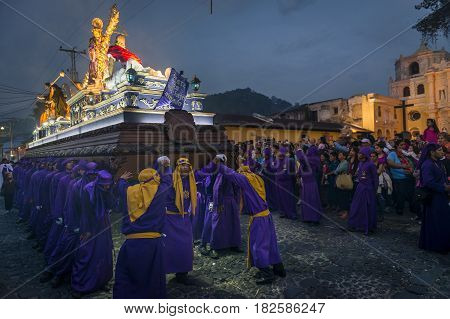 Antigua Guatemala - April 17 2014: Penitents carrying a float with the image of Jesus Christ in an Easter procession at night during the Holy Week in Antigua Guatemala