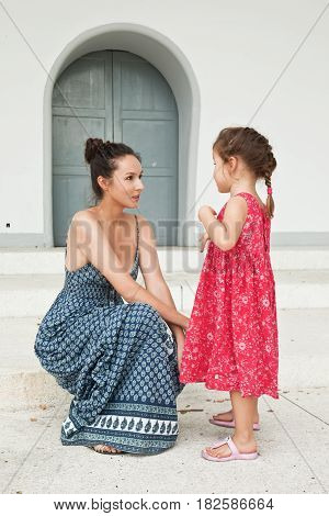 Young woman talks with a child. Portrait of a young family