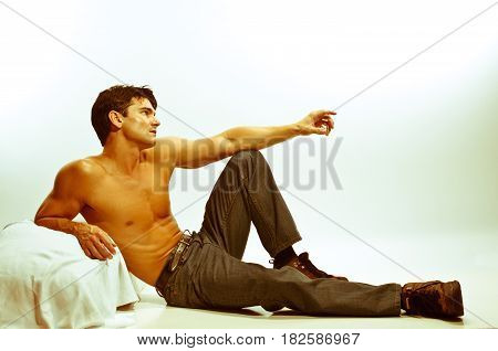 The sexy man is laying back pointing out at the sky.