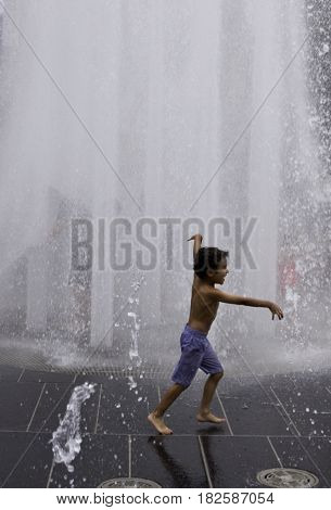 Montreal, Quebec - June 27, 2015 - Vertical of a little boy running across the automated water fountains at the International Jazz Festival in downtown Montreal, Quebec on a bright day at the end of June.