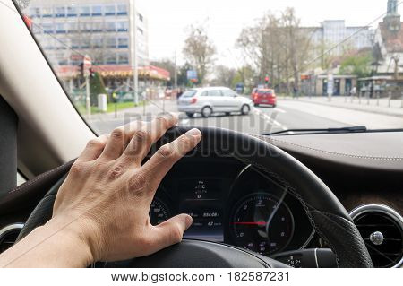 Steerind Wheel With Driver Hand On It In Modern Car Interior With View Of Street