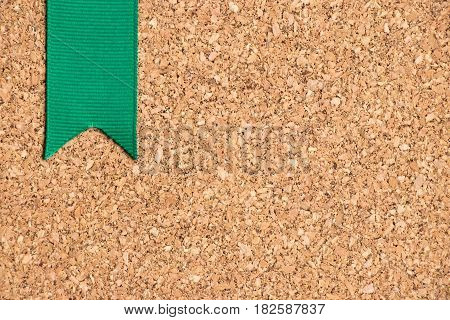Green ribbon on cork board texture background