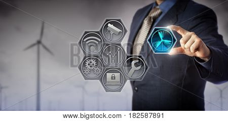 Blue chip business manager monitoring and controlling wind farm infrastructure via an internet of things application matrix. Renewable energy and Internet of Things concept for wind farm management.