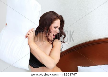 portrait of woman fighting with pillow in bed