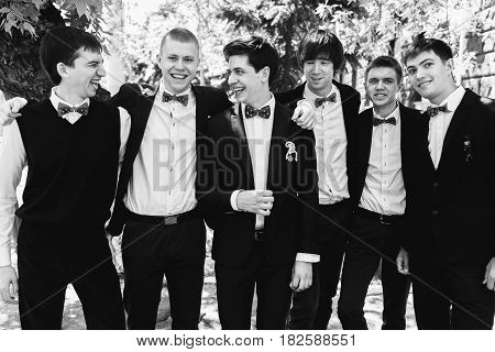 Black and white picture of groom standing with groomsmen