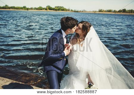 Groom Takes Bride's Hand And Kisses Her Tender While Wind Blows Her Veil Away