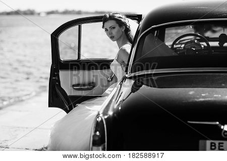 Bride sits in an open car while wind blows around it