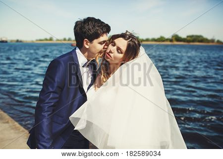 Groom Leans To Bride's Face While She Enjoys A Wind With Closed Eyes