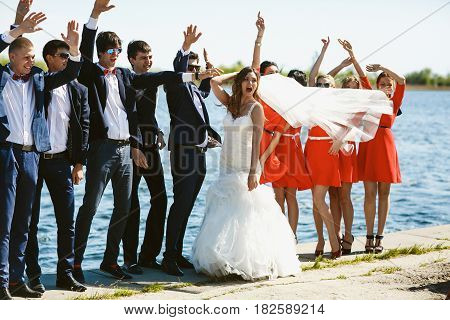 Wind blows bride's veil on the bridesmaids while they stand together on the shore