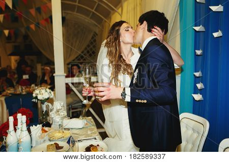Just Married Couple Kiss Holding Glasses With Drinks In Their Arms