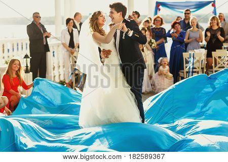 Bridesmaids make waves of blue cloth veil newlyweds dance on it