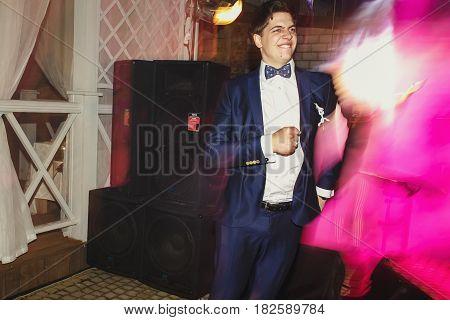 Pink disco light highlights funny dancing groom