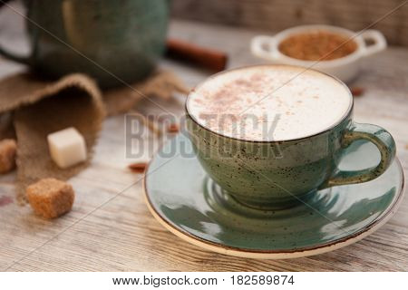 Cup of Cappuccino on wooden table and pieces of sugar