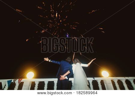 Bride and groom greet sparkling firework on the street