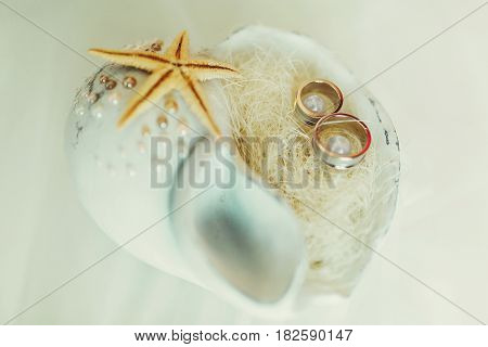 Wedding rings lie in a white cockleshell with little pearls