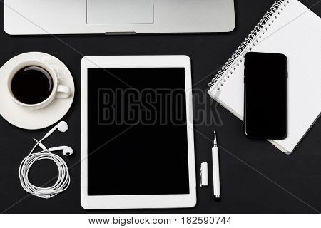 Office workplace with text space. Top view of office dark desk table with laptop, phone, tablet, notebook, and coffee cup. Top view with copy space Modern office workplace.