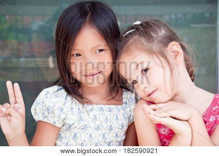 Portrait of wo little asian girlfriends, mix faces