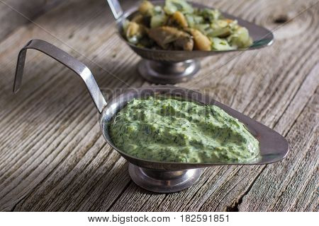 Homemade sauce with basil in white mortar on an old wooden table.
