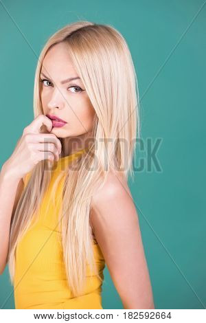 sexy red lips on face of pretty girl or sexy woman young fit fashion model with beautiful makeup blond long hair hairstyle posing in yellow bodysuit on green background