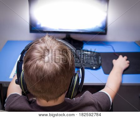 Back of the head view of a teenager playing a computer game at home. He is wearing a headset. The screen blasts.