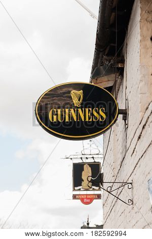 Chirk United Kingdom - March 31 2016: Old Guinness sign outside a pub or bar first brewed in 1759 owned by Diageo beverages it is one of the worlds most successful beer brands worldwide