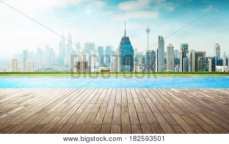 Empty wooden deck with swimming pool Beautiful pool side view with city skyline .
