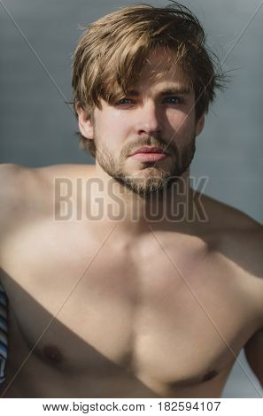 fit muscular man with beard or sexy macho athlete with sunlight on naked torso on grey background. Blond hair and bearded unshaven face skin. Male beauty and fitness