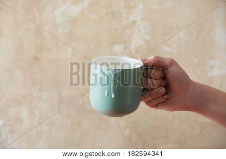 Blue cup with kefir butter milk yogurt or turkish drink ayran natural dairy product in female hand on beige wall background. Dieting and healthy eating