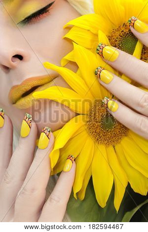Summer yellow makeup and manicure with a design on the nails on the woman with sunflowers closeup.Nail art.