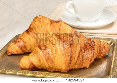 A photo of fresh croissants on a vintage tray, with a place for text and a cup of coffee in the background