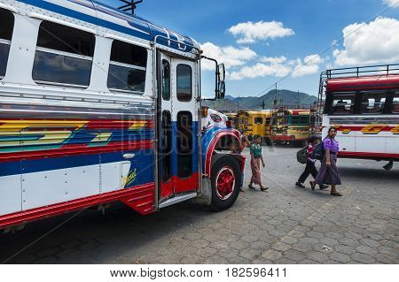 Antigua Guatemala - April 19 2014: Family in a bus terminal with colorful buses in Antigua Guatemala
